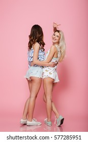 Back view of two happy beautiful young women looking back and showing peace sign over pink background
