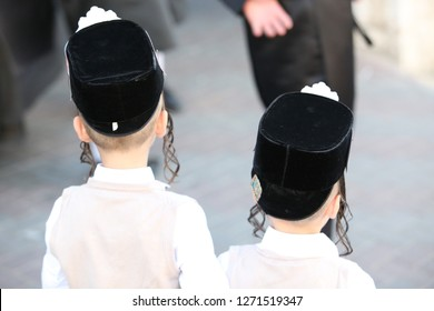 Back view of two hasidic children with their  small fur hats and side curls