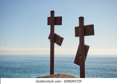 Back view of two iron poles with wooden signboards against endless rippled sea and clear blue sky on sunny summer day.