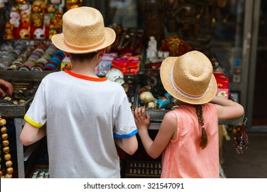 Back view of two kids brother and sister at flea market