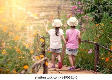 Back view of two little girls holding hand and walking together in the garden in vintage color tone