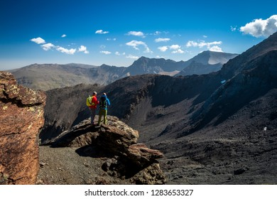 Back view of two male travelers standing on rock and looking at magnificent mountains on beautiful sunny day in Sierra Nevada, Granada, Spain