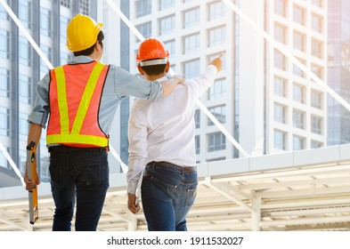 Back view of two male wearing safety helmet and looking at modern building. Construction foreman wearing orange safety vest with yellow reflective stripe and holding spirit level while project enginee