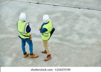 Back view of two men in helmets and waistcoats examining construction site during inspection