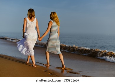 Back view of two woman on holiday travel vacation beach. Blue sunny ocean sky background
