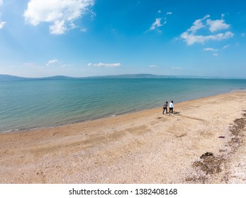 Back view of two women standing on beach and looks at sea against blue sky in Holywood, Northern Ireland, aerial view