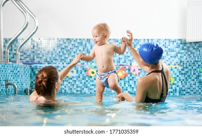 Back view of two women in swimming pool helping a small boy keep balance in water, smiling baby is standing in their hands. Concept of sport for kids