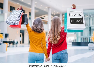 Back view of two young casually dressed women holding bunches of shopping bags in hands while wallking in the mall. Black friday sales concept.