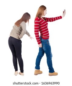 Back view of two young woman photographed on a mobile phone in sweater. Rear view people collection. backside view of person. Rear view. Isolated over white background.