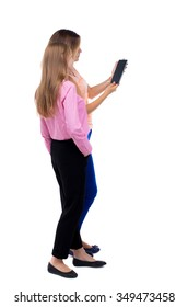Back view of two young woman look at smart phone. Rear view people collection.  backside view person. Rear view. Isolated over white. Two girls blonde stand cancer looking at tablet computer