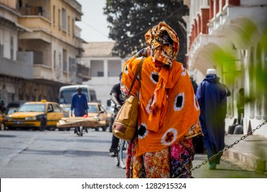 Back view of a typical african woman dressed in colorful  orange clothing on the streets of Sant Louis, Senegal during midday.
