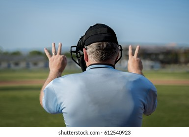 Back view of umpire making call at home plate.Three balls, two strikes