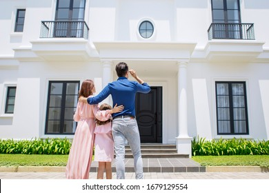 Back view of unidentified family group holding & hugging each other while looking at the new house and standing on its yard