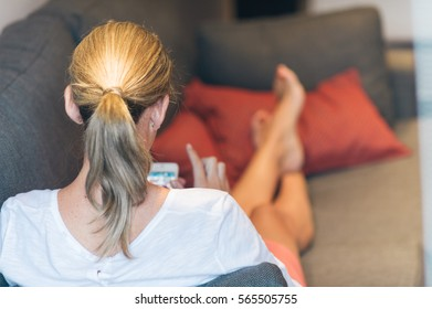 Back view of unrecognizable blonde woman on couch browsing the Internet via cell phone.
