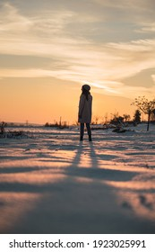 Back view of unrecognizable female in warm outfit standing alone among snowy meadow and admiring picturesque sunset in winter countryside