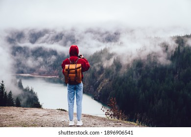 Back view of unrecognizable person in jeans standing alone on stony edge of cliff among lake and taking shots of waterscape