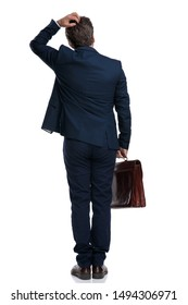 Back view of an unsure businessman scratching his head and holding his briefcase while wearing an elegant blue suit and standing on white studio background