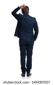 Back view of an unsure businessman scratching his head and holding his hand in his pocket while wearing a blue suit and standing on white studio background