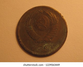 Back view of USSR coin. Kopecks from Soviet Union. Great for numismatic collection. Shiny coin isolated on yellow surface of paper. Histirical retro coin of kopek (cent).