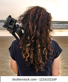 Back view of very attractive model on her solo trip, an independent girl with beautiful, golden and curly hair, holding tripod on her shoulder, assisting as intern in photoshoot at beach during sunset
