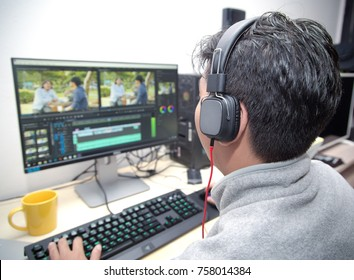 back view of video editor using computer at home