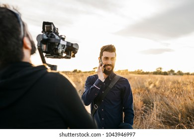 Back view of videographer with camera taking video of handsome bearded man.