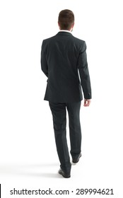 back view of walking businessman in black suit. isolated on white background