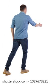 Back view of a walking businessman who stretches his hand for a handshake. Rear view people collection. Isolated over white background. A guy in a short sleeve shirt walks forward in greeting.