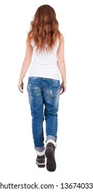 back view walking  leggy woman. beautiful redhead girl in motion. backside view person. Rear view people collection. Isolated over white background. trendy teen girl goes in mountain boots and jeans