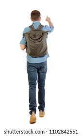 Back view of a walking man with a bag pointing his hand up. backside view of person.  Rear view people collection. Isolated over white background. A traveler in a shirt looks at the sights