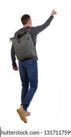 Back view of a walking man with a bag pointing his hand up. backside view of person. Isolated over white background. Stylish guy in boots and with a backpack goes showing his hand in the sky.