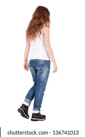 back view walking  woman. beautiful redhead girl in motion. backside view of person.  Rear view people collection. Isolated over white background. Stylish teenage girl in boots and vest goes forward