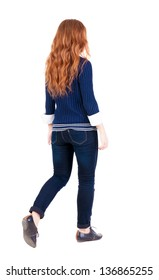 back view walking woman. beautiful redhead girl in motion. backside view person.  Rear view people collection. Isolated over white . A girl in a blue sweater and a white shirt is moving forward