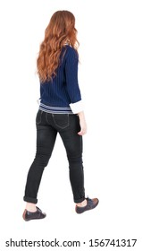 back view walking woman. beautiful redhead girl in motion. backside view person.  Rear view people collection. Isolated over white background. girl in blue sweater and a white shirt is moving forward