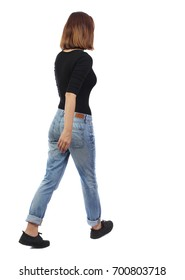 back view of walking  woman. beautiful blonde girl in motion.  backside view of person.  Rear view people collection. The girl in the black sweater and jeans goes to the right.