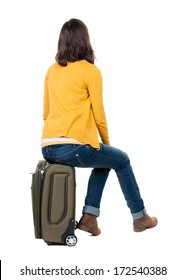 back view of walking  woman  in cardigan sits on a suitcase. beautiful  girl in motion.  backside view of person.  Rear view people collection. Isolated over white background.