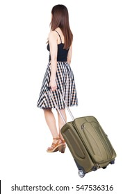 back view of walking woman  with green suitcase. beautiful brunette girl in motion.  backside view of person. Isolated over white background. girl on the heels of a suitcase rolls