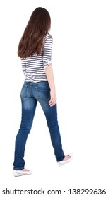 back view walking woman in jeans beautiful brunette girl in motion. backside view person. Rear view people collection. Isolated over white. girl in striped T-shirt with sleeves podkatannymi goes ahead