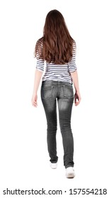 back view of walking  woman in jeans. backside view of person.  Rear view people collection. Isolated over white background. The girl in a striped T-shirt with sleeves podkatannymi goes ahead