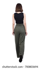 back view of walking  woman in pants. beautiful girl in motion.  backside view of person.  Rear view people collection. Isolated over white background. girl in the green trousers slowly goes forward