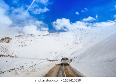 Back view of white cars on the road in the mountains with snow durindg winter season of Leh Ladakh, India. Concept about dream destination with bue sky background.Focus on life goal with copy space.