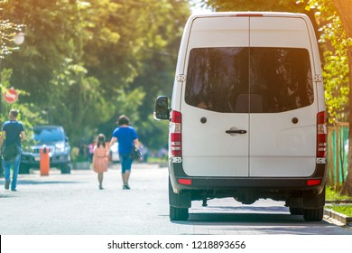 Back view of white passenger medium size commercial luxury minibus van parked n shadow of green tree on summer city street i with blurred silhouettes of pedestrians and cars under green trees.