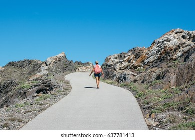 Back view of a woman with backpack taking walk on empty path in mountains.