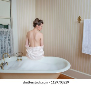 Back view of woman with bare shoulders sitting on edge of antique tub full of bubbles