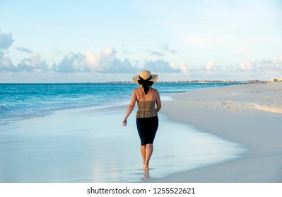 Back View of a Woman in Black Pencil Skirt, Leopard Tank Top and Straw Hat Walking Barefoot on a Caribbean Beach