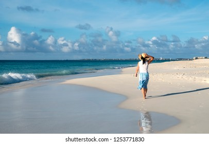 Back View of a Woman in Blue Skirt, White Top and Straw Hat Walking Barefoot on a Caribbean Beach on a Sunny Day