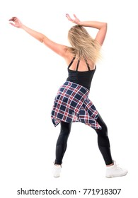 Back view of woman dancing enjoying music with raised arms and flowing tousled hair. Full body length portrait isolated on white background.