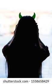 back view of woman with devils horns on head