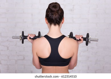 back view of woman doing exercises with dumbbells over white brick wall