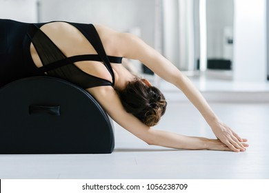 Back view of woman doing reformer pilates stretching exercise.